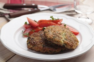 Fish cakes with tomato salad on a plate